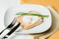 Λαθραίο αυγό στη φρυγανιά με τα φρέσκα κρεμμύδια λευκό πιάτων Στοκ φωτογραφία με δικαίωμα ελεύθερης χρήσης