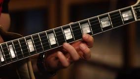 Λαιμός κιθάρων κινηματογραφήσεων σε πρώτο πλάνο και χέρι κιθαριστών απόθεμα βίντεο
