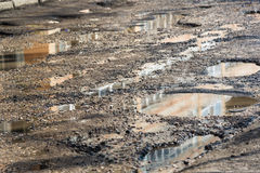 Λακκούβες στο δρόμο ασφάλτου που γεμίζουν με το νερό Στοκ Φωτογραφίες