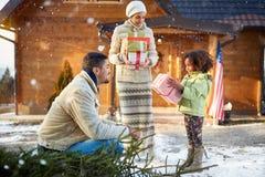 Λαμβανόμενα μικρό κορίτσι χριστουγεννιάτικα δώρα από τους γονείς στοκ φωτογραφίες