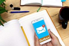 Λαμβανόμενο μήνυμα ηλεκτρονικού ταχυδρομείου στο κινητό τηλέφωνο Γυναίκα που κρατά ένα άσπρο κινητό τηλέφωνο στο υπόβαθρο του εργ Στοκ Εικόνες