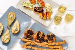 Λαμπιρίζοντας κρασί και πρόχειρα φαγητά σε έναν ξύλινο άσπρο πίνακα Στοκ φωτογραφία με δικαίωμα ελεύθερης χρήσης