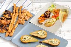 Λαμπιρίζοντας κρασί και πρόχειρα φαγητά σε έναν ξύλινο άσπρο πίνακα Στοκ εικόνες με δικαίωμα ελεύθερης χρήσης