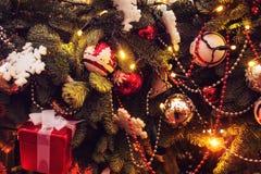 Λαμπιρίζοντας νέα γιρλάντα έτους στο χριστουγεννιάτικο δέντρο Χριστουγεννιάτικο δέντρο που διακοσμείται με τις χρυσές και ασημένι στοκ εικόνα