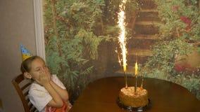 Λαμπιρίζοντας πηγές πυρκαγιάς σε ένα κέικ Το κέικ είναι στον πίνακα μπροστά από το κορίτσι Γενέθλια κοριτσιών Κέικ με τα φω'τα Το φιλμ μικρού μήκους