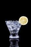 Λαμπιρίζοντας ποτό σε ένα martini γυαλί με τη φέτα λεμονιών σε ένα BL Στοκ Εικόνες
