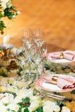 Λαμπιρίζοντας στάσεις γυαλικών στον πίνακα που προετοιμάζεται για τον κομψό γάμο Στοκ Φωτογραφία