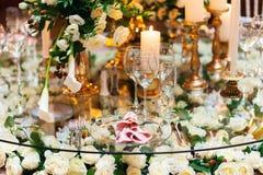Λαμπιρίζοντας στάσεις γυαλικών στον πίνακα που προετοιμάζεται για τον κομψό γάμο Στοκ Εικόνες