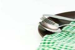 Λαμπρά ανοξείδωτα δίκρανο, μαχαίρι και κουτάλι στο καφετί πιάτο Στοκ εικόνα με δικαίωμα ελεύθερης χρήσης