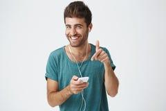 Λαμπρά να χαμογελάσει ο ισπανικός τύπος στην μπλε μπλούζα, κρατώντας το smartphone, μουσική ακούσματος με τα ακουστικά, που γελά  Στοκ εικόνα με δικαίωμα ελεύθερης χρήσης