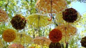 Λαμπρά πορτοκαλιές και κίτρινες ομπρέλες και σφαίρες που κρεμούν και που κινούνται στον αέρα απόθεμα βίντεο