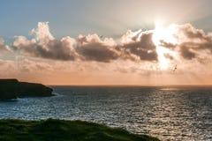 Λαμπρά σύνολα ήλιων καύσης κατά μήκος της τραχιάς ακτής της επικεφαλής χερσονήσου βρόχων της Ιρλανδίας ` s, κομητεία Clare, Ιρλαν στοκ φωτογραφία