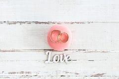Λαμπρά χρυσά γαμήλια δαχτυλίδια στο ρόδινο macaron και και το σύμβολο αγάπης Στοκ φωτογραφία με δικαίωμα ελεύθερης χρήσης