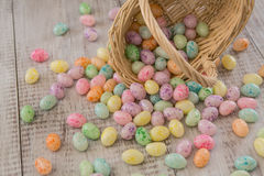 Λαμπρά χρωματισμένη καραμέλα αυγών Πάσχας που ανατρέπει από το ψάθινο καλάθι Στοκ εικόνα με δικαίωμα ελεύθερης χρήσης