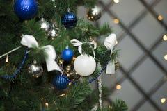 Λαμπρή ένωση σφαιρών Χριστουγέννων άσπρη στους κλάδους πεύκων με το εορταστικό υπόβαθρο στοκ εικόνα με δικαίωμα ελεύθερης χρήσης
