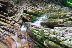 Λαμπροί βράχοι με το παλαιό βρύο και τα ρέοντας ρεύματα του κολπίσκου βουνών Στοκ φωτογραφία με δικαίωμα ελεύθερης χρήσης