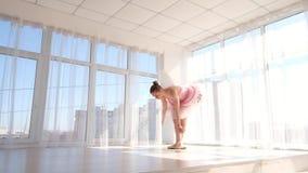 Λαμπρός θηλυκός χορευτής μπαλέτου στο ρόδινο tutu που ασκεί και που χαμογελά απόθεμα βίντεο
