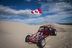 Λαμπρός κόκκινος αμμόλοφος άμμου με λάθη που σταθμεύει στην άμμο στοκ φωτογραφίες