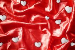 Λαμπρός χαλκός φύλλων αλουμινίου καρδιών στο κόκκινο μετάξι υφάσματος Στοκ εικόνα με δικαίωμα ελεύθερης χρήσης