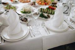Λαμπρό διακοσμημένο επιτραπέζιο σκεύος μαχαιροπήρουνων με τα τρόφιμα στον πίνακα Στοκ Φωτογραφίες