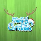 Λαμπρό κείμενο Χαρούμενα Χριστούγεννας με τα Χριστούγεννα ΚΑΠ και κέρατο ταράνδων πέρα από το ξύλινο υπόβαθρο Στοκ Εικόνες