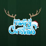 Λαμπρό κείμενο Χαρούμενα Χριστούγεννας με τα Χριστούγεννα ΚΑΠ και κέρατο ταράνδων πέρα από το ξύλινο υπόβαθρο Στοκ εικόνες με δικαίωμα ελεύθερης χρήσης