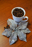 Λαμπρό λουλούδι κοντά στο φλυτζάνι με το φασόλι καφέ Στοκ Εικόνα