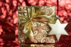 Λαμπρό χρυσό δώρο με την κορδέλλα και το αστέρι στοκ εικόνα