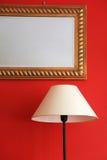 Λαμπτήρας και πλαισιωμένος καθρέφτης στον κόκκινο μοντέρνο τοίχο Στοκ φωτογραφίες με δικαίωμα ελεύθερης χρήσης
