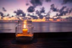 Λαμπτήρας κεριών στον πίνακα με τη θάλασσα και το υπόβαθρο ηλιοβασιλέματος στοκ εικόνες με δικαίωμα ελεύθερης χρήσης