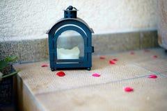 Λαμπτήρας με ένα κερί και τα κόκκινα πέταλα Στοκ Εικόνες