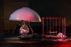 Λαμπτήρας με γυαλιού lampshade και Newton τις σφαίρες στον πίνακα στοκ εικόνες