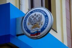 Λαμπτήρας με το λογότυπο της φορολογικής υπηρεσίας της Ρωσικής Ομοσπονδίας στον τοίχο του κτηρίου στοκ φωτογραφία