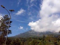 Λαμπτήρας οδών και άσπρο όμορφο σύννεφο επάνω από το βουνό στοκ εικόνα
