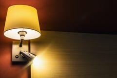 Λαμπτήρας πέρα από το κρεβάτι στο δωμάτιο ή το δωμάτιο ξενοδοχείου Στοκ Φωτογραφία