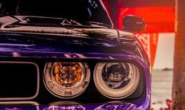 Λαμπτήρας προβολέων κινηματογραφήσεων σε πρώτο πλάνο του πορφυρού κλασικού εκλεκτής ποιότητας αυτοκινήτου στο θολωμένο κόκκινο υπ Στοκ φωτογραφία με δικαίωμα ελεύθερης χρήσης