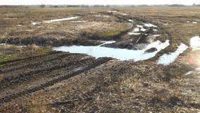 Λασπώδης βρώμικος δρόμος με τις λακκούβες μέσω του τομέα φιλμ μικρού μήκους