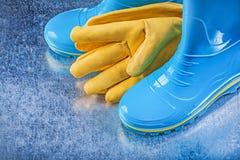 Λαστιχένια γάντια δέρματος μποτών στο μεταλλικό υπόβαθρο που καλλιεργεί con Στοκ Εικόνα