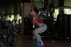 Λατίνα γυναίκα που κάνει τη στάση οκλαδόν Barbell άσκησης Στοκ φωτογραφία με δικαίωμα ελεύθερης χρήσης