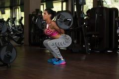 Λατίνα γυναίκα που κάνει τη στάση οκλαδόν Barbell άσκησης Στοκ εικόνες με δικαίωμα ελεύθερης χρήσης