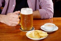 Λατινική μπύρα κατανάλωσης ατόμων και κατανάλωση των πρόχειρων φαγητών σε έναν φραγμό Στοκ Φωτογραφία