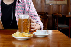 Λατινική μπύρα κατανάλωσης ατόμων και κατανάλωση των πρόχειρων φαγητών σε έναν φραγμό Στοκ Εικόνες
