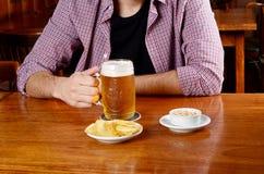 Λατινική μπύρα κατανάλωσης ατόμων και κατανάλωση των πρόχειρων φαγητών σε έναν φραγμό Στοκ φωτογραφία με δικαίωμα ελεύθερης χρήσης