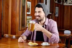 Λατινική μπύρα κατανάλωσης ατόμων και κατανάλωση των πρόχειρων φαγητών σε έναν φραγμό Στοκ εικόνα με δικαίωμα ελεύθερης χρήσης