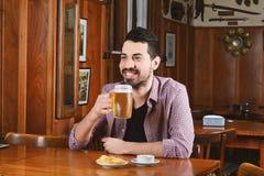 Λατινική μπύρα κατανάλωσης ατόμων και κατανάλωση των πρόχειρων φαγητών σε έναν φραγμό Στοκ Φωτογραφίες