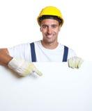 Λατινικός εργάτης οικοδομών με το σημάδι για τη διαφήμιση Στοκ Φωτογραφία