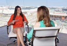 Λατινικός θηλυκός παρουσιαστής που παίρνει συνέντευξη από μια ξανθή προσωπικότητα στο stu TV Στοκ Φωτογραφία