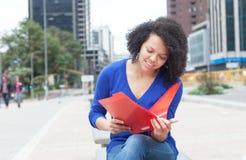 Λατινικός σπουδαστής με το σγουρό έγγραφο ανάγνωσης τρίχας στην πόλη Στοκ εικόνες με δικαίωμα ελεύθερης χρήσης