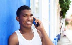 Λατινικός τύπος που μιλά στο τηλέφωνο μπροστά από έναν μπλε τοίχο Στοκ Φωτογραφίες