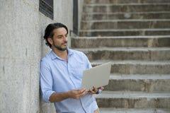 Λατινικό άτομο στη σκάλα πόλεων που λειτουργεί με το φορητό προσωπικό υπολογιστή που φαίνεται ικανοποιώ και βέβαιο Στοκ φωτογραφία με δικαίωμα ελεύθερης χρήσης